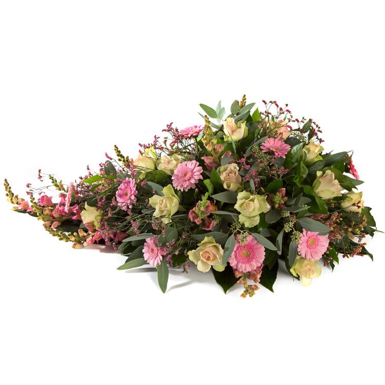 Langwerpig rouwstuk roze tinten met oa Germini en Rozen